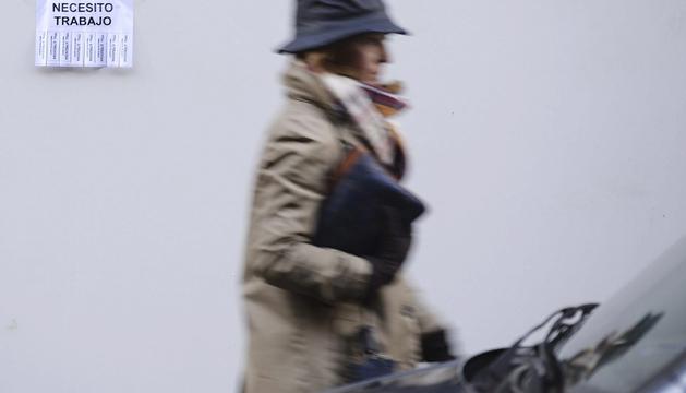 Una mujer pasea por una calle de Valladolid al lado de un cartel de búsqueda de trabajo