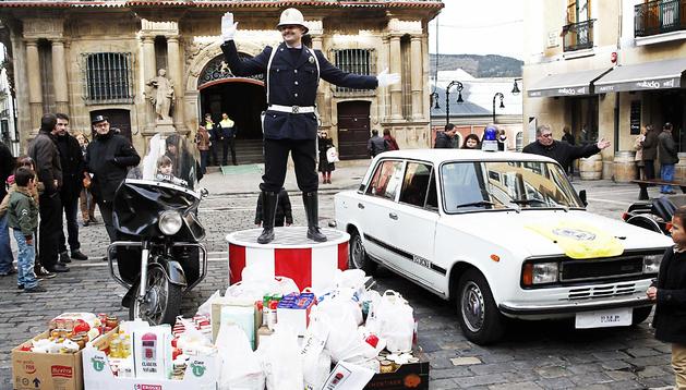 El guardia municipal uniformado como en los años 60 simula regular el tráfico junto a un coche y una moto de la época