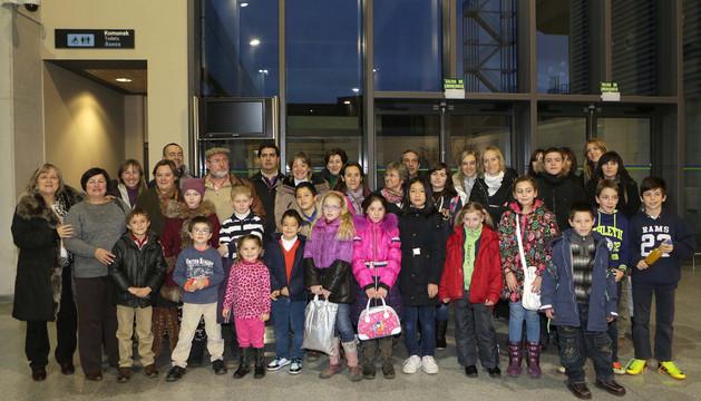 Los niños posan junto a sus familias de acogida en el aeropuerto de Noáin