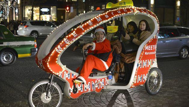 Un velo-taxi decorado con motivos navideños circula por una calle de Tokio