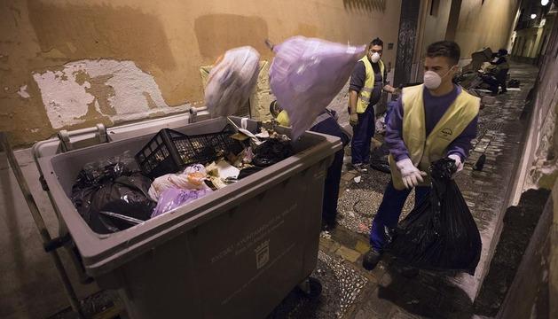 Trabajadores de un servicio de recogida de residuos trabajan  tras ser contratados por las Asociaciones de Empresarios de Hostelería
