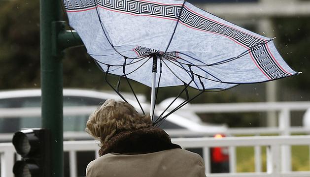 Una mujer sujeta con sus manos el paraguas en Pamplona.