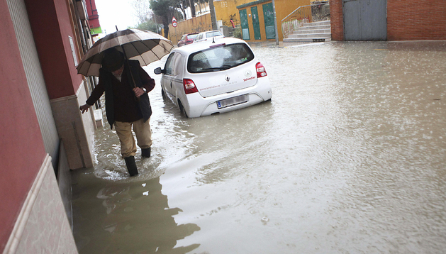 Un hombre pasa por una de las calles totalmente anegada en Algeciras (Cádiz)