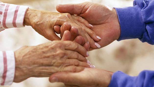 Una anciana se agarra a otra personas en un gesto de apoyo y confianza