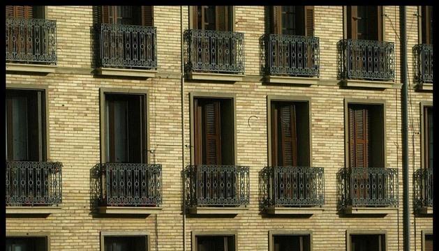 Una vivienda anuncia su venta en un edificio antiguo