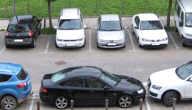 Varios coches aparcados en una calle.