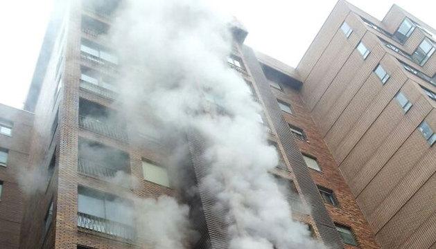 Una intensa humareda sale del piso afectado por el fuego
