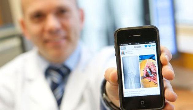 El doctor Gonzalo Mora muestra la aplicación en la pantalla de un smartphone.