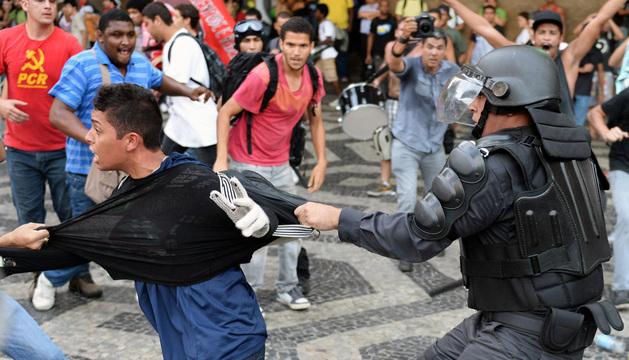 Un policía agarra a un manifestante durante la protesta contra el precio del bus en Brasil.