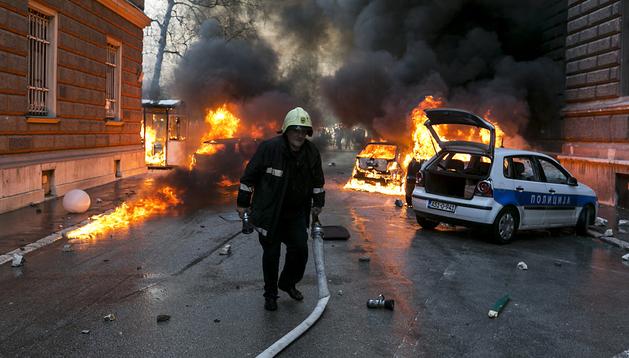 Imagen de los coches de la policía ardiendo durante el asalto al consulado de Sarajevo durante una manifestación ante la sede del Gobierno cantonal de Sarajevo