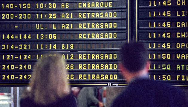 Dos viajeros observan un panel de información en Barajas.