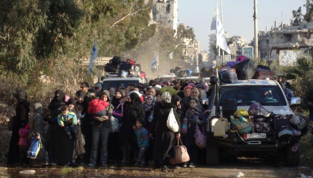 Civiles sirios evacuados durante este domingo de la ciudad de Homs
