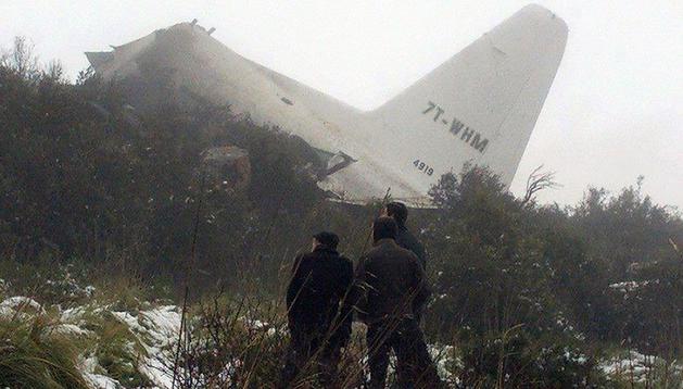 Tres personas observan los restos del avión siniestrado en Argelia