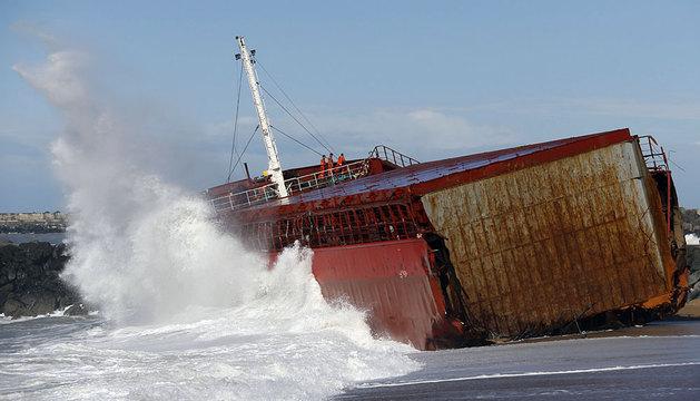 Varias personas realizan las labores de extracción de combustible en el carguero