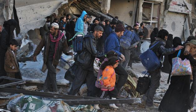 Ciudadanos sirios abandonaban este martes las zonas bombardeadas de Homs para recibir ayuda humanitaria.
