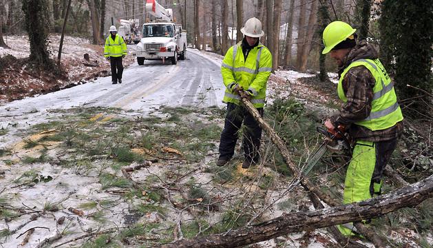 Un grupo de trabajadores retira un árbol caído de una carretera en Smyrna, Georgia (Estados Unidos)