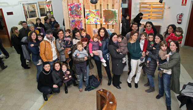 Niños participantes en el curso junto a familiares y parte de las obras que se exponen
