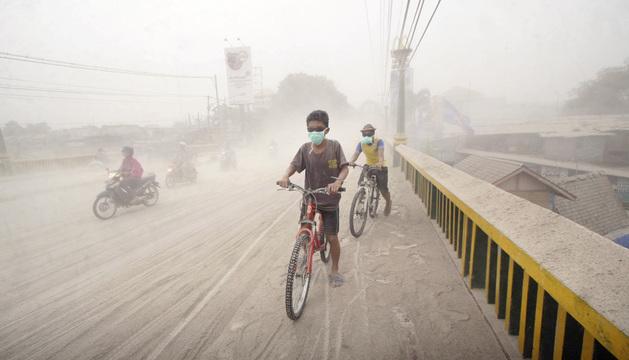 Varios estudiantes circulan en bici bajo una intensa niebla provocada por la ceniza volcánica.