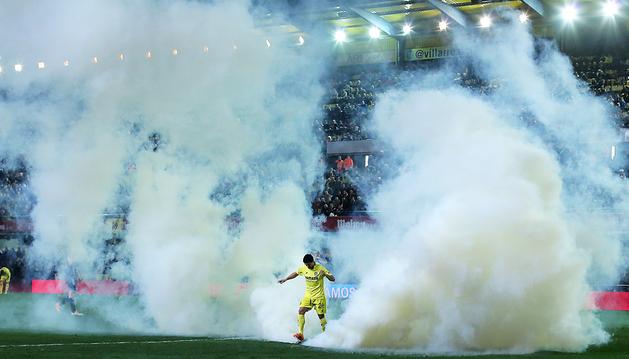 Jonathan Pereira, del Villarreal, trata de retirar el bote de humo del césped