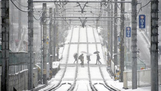 Varias personas cruzan una vía de ferrocarril cubierta de nieve, en Tokio