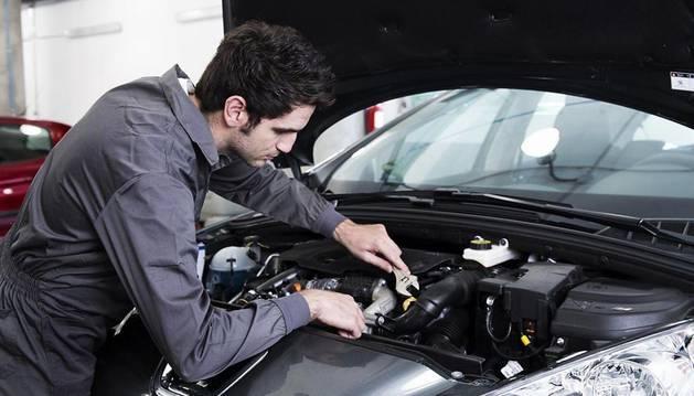 Un mecánico revisa el motor de un coche en un taller de reparaciones