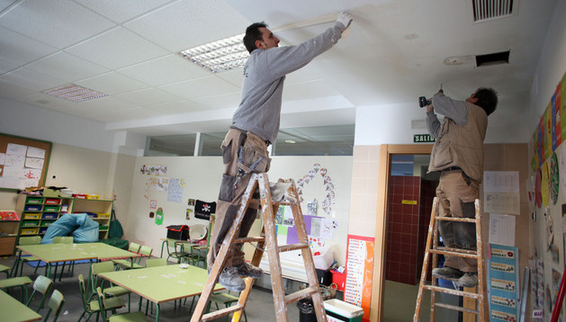 Dos operarios reparan el techo de una de las aulas del colegio Huertas Mayores afectadas por las fugas