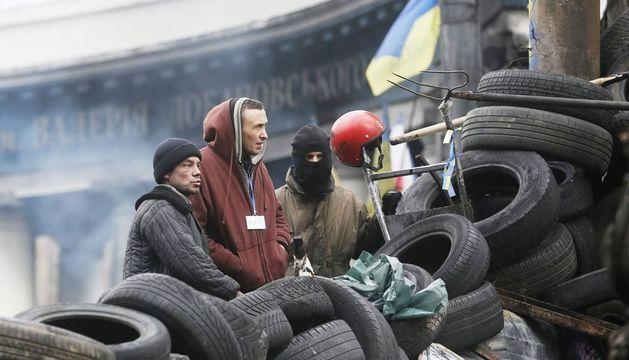 Unos manifestantes permanecen de pie en una barricada en la calle Grushevskogo, en el centro de Kiev
