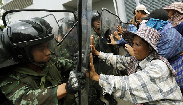 Soldados intentan controlar a los agricultores que se manifiestan durante una protesta a las puertas de la Secretaría de Defensa.