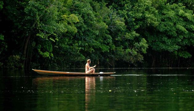 Una turista navega por un afluente del río Negro en la Amazonía brasileña