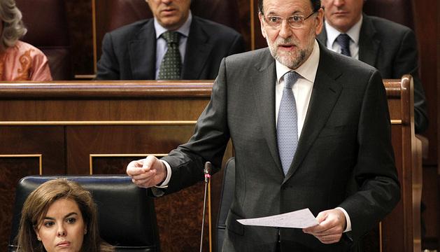 El presidente del Gobierno, Mariano Rajoy, junto a la vicepresidenta, Soraya Sáenz de Santamaría, durante su intervención.