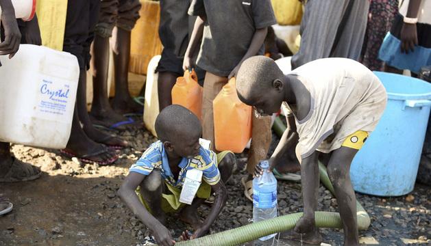 Dos niños llenan una botella de agua en un área de protección de la ONU en Sudán del Sur.