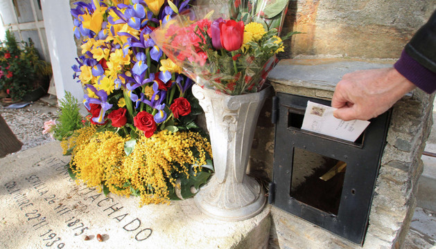 Un hombre introduce una una carta al fallecido poeta Antonio Machado en un buzón fijo a su tumba, en Collioure (sur de Francia).