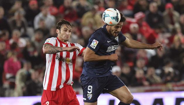El delantero paraguayo del Málaga Santa Cruz (d) cabecea un balón ante el argentino Marco Torsiglieri, del Almería