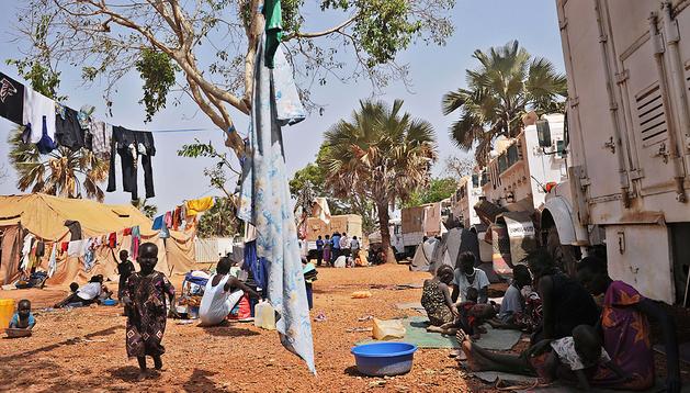 Varios niños y sus familiares juegan en un campamento de Sudán del Sur durante la visita de una misión de la ONU