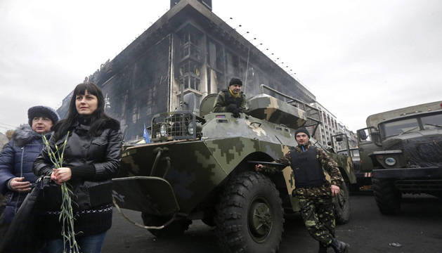 Unas mujeres sostienen claveles ante un vehículo militar en la Plaza de la Independencia en Kiev.