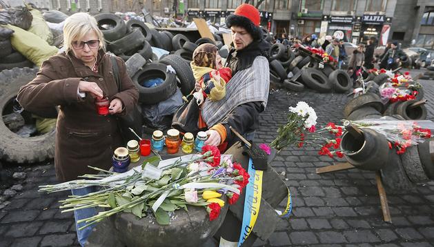 Varias personas colocan flores y velas en memoria de los caídos durante los sangrientos enfrentamientos ocurridos en Kiev, Ucrania
