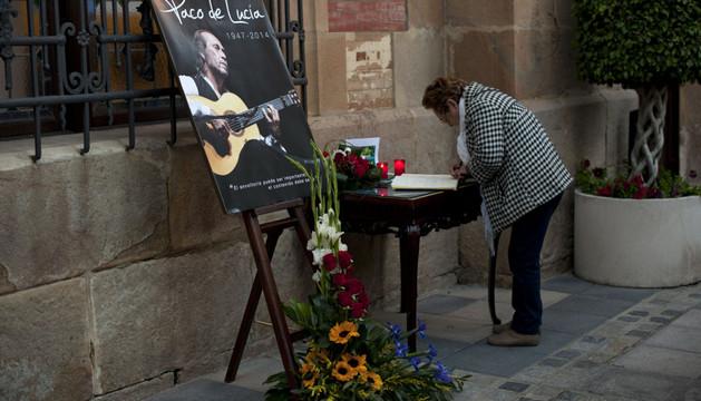 Una mujer firma en un libro de condolencias por la muerte de Paco de Lucía