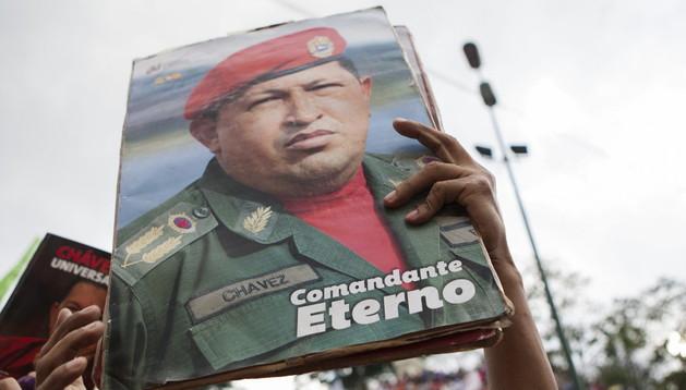 Una mujer muestra una fotografía del fallecido presidente Hugo Chávez.