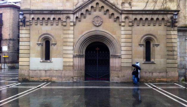 Un turista pasea este sábado bajo la lluvia frente a la iglesia de San Lorenzo, en el centro de Pamplona.