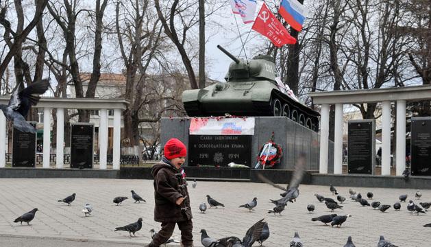 Un niño juega frente a un monumento de un tanque militar en Simferópol, decorado con la bandera soviética y la del Partido del Bloque Ruso.