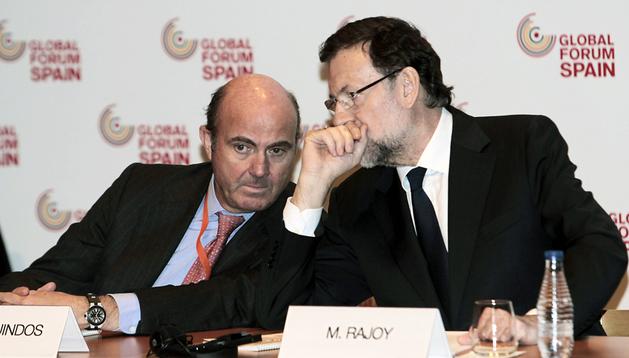 El presidente del Gobierno, Mariano Rajoy (dcha.), conversa con el ministro de Economía, Luis de Guindos, durante la clausura en el Foro Global España 2014