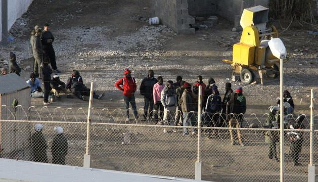 Inmigrantes subsaharianos rodeados por la Policía marroquí, en el perímetro fronterizo entre Ceuta y Marruecos