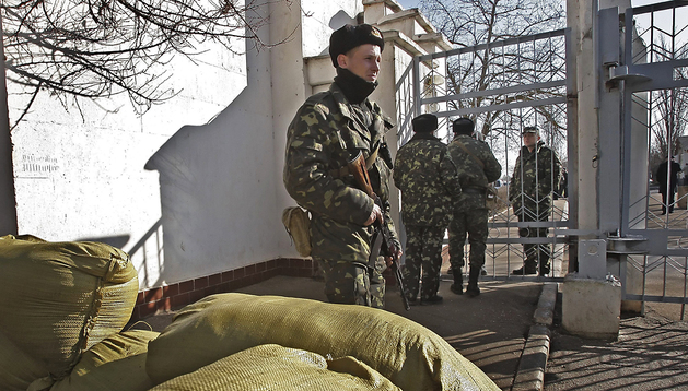 Soldados armados sin identificar, presuntamente rusos, vigilan la entrada de la base naval ucraniana de Novoozerniy