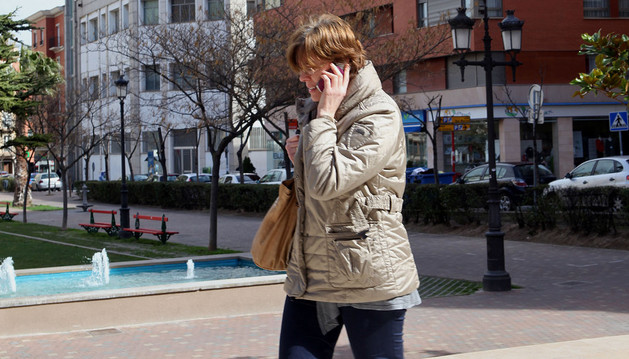 Una mujer habla por su móvil en el paseo de Invierno con la torre de Telefónica, al fondo