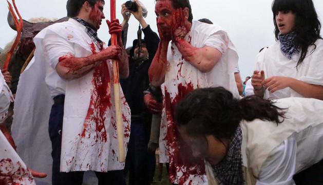 Varios jóvenes se embardunan con sangre en el ritual previo a la salida de la mascarada popular por las arterias principales de Alsasua