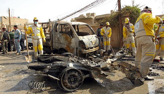 Trabajadores municipales junto a uno de los coches bomba en Bagdad.