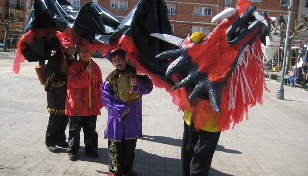 Un grupo de niños disfrazados de chinos portando un colorido dragón