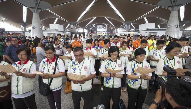 Un grupo de budistas reza en el aeropuerto de Kuala Lumpur por las víctimas del accidente
