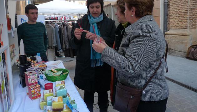 Amets Valencia Ilundáin, de la franquicia Equivalenza, atienda a unas clientes en la calle Comercio. A su lado, el otro socio en el negocio Iban Arbizu Leza