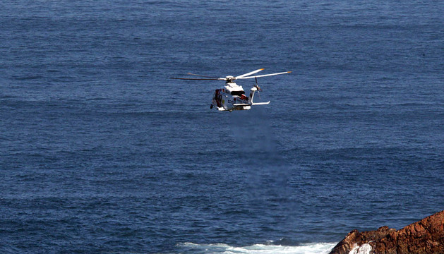 Un helicóptero sobrevuela al pesquero hundido.